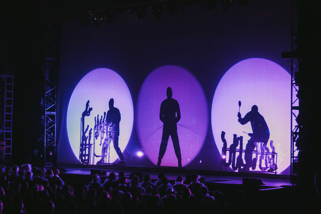 The Blue Man Group open in silhouette, playing their signature percussion instruments. |Cam Peters