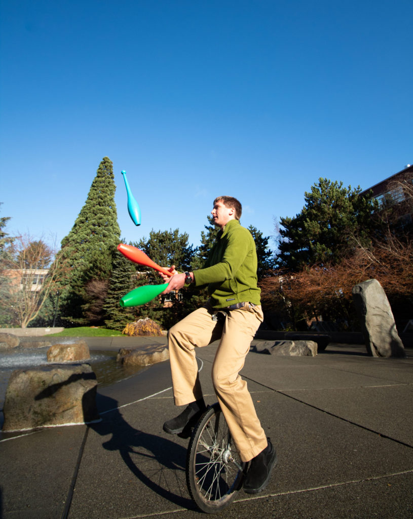 Professor Eric Gilbertson juggles pins while riding a unicycle.
