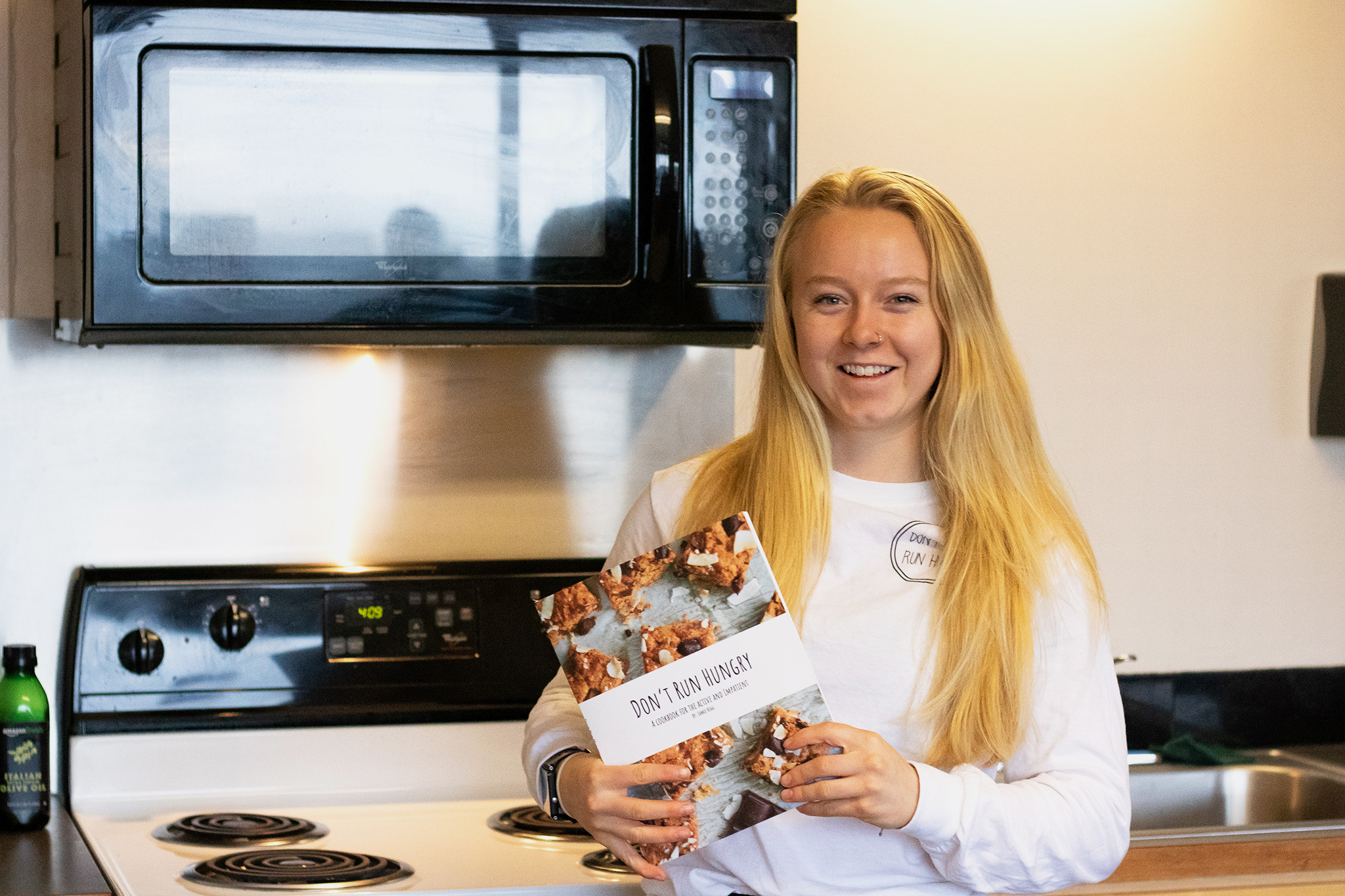 Jamie Hegg, sophmore track and field athlete, proudly holds her now published cook book, named Dont Run Hungry.
