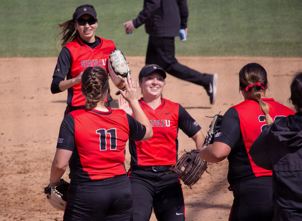 Women's Softball celebrates after a successful inning.