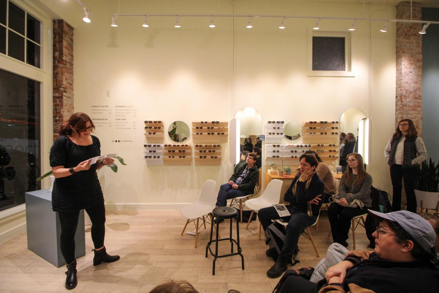 """A crowd of onlookers listens to Jessica Mooney as she reads from her book, """"Parting Gifts for Losing Contestants."""""""