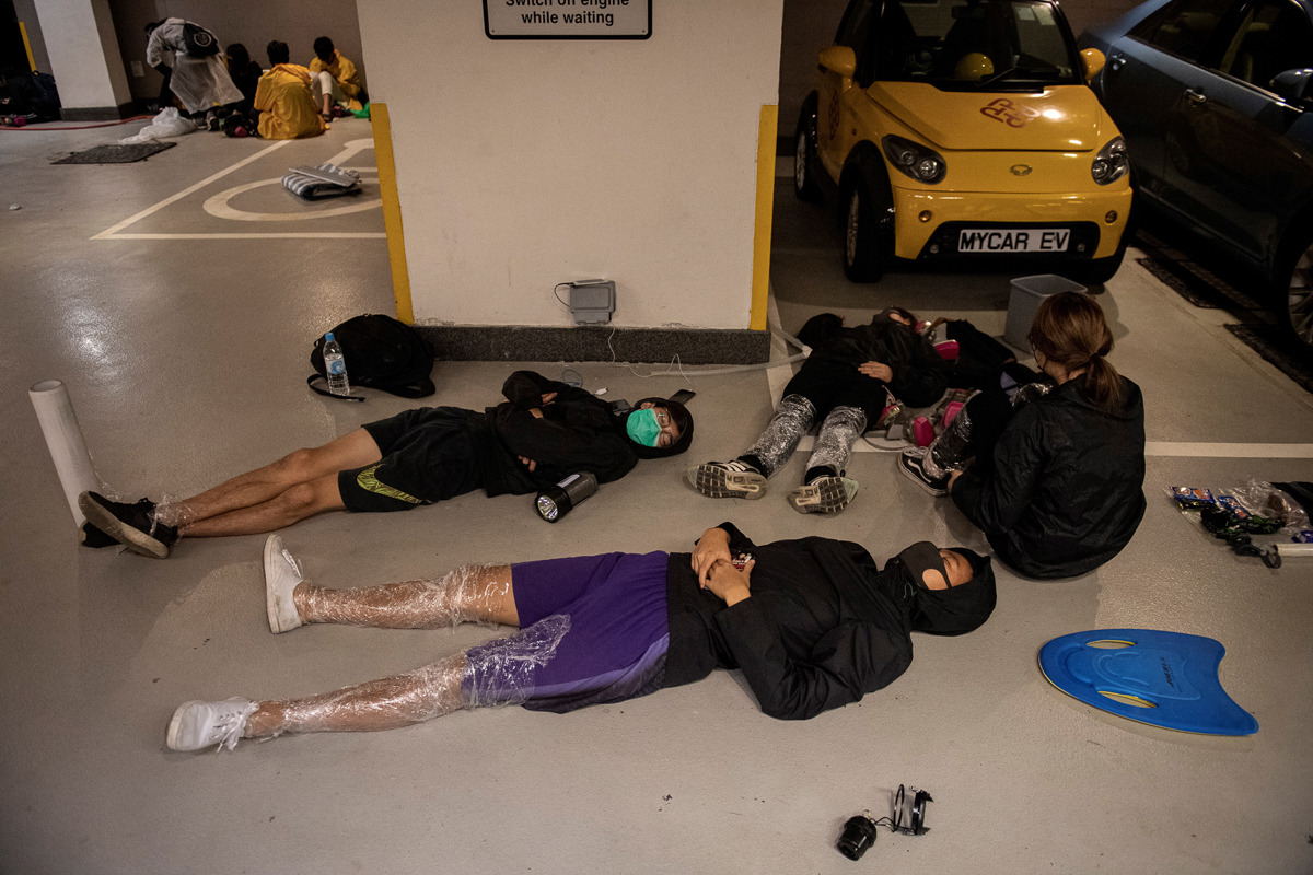 Hong Kong Polytechnic University protestors resting on the floor of a parking garage