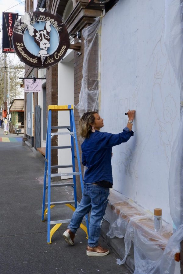 Morgan Zion paints her three-panel mural on the front of a boarded-up Molly Moons