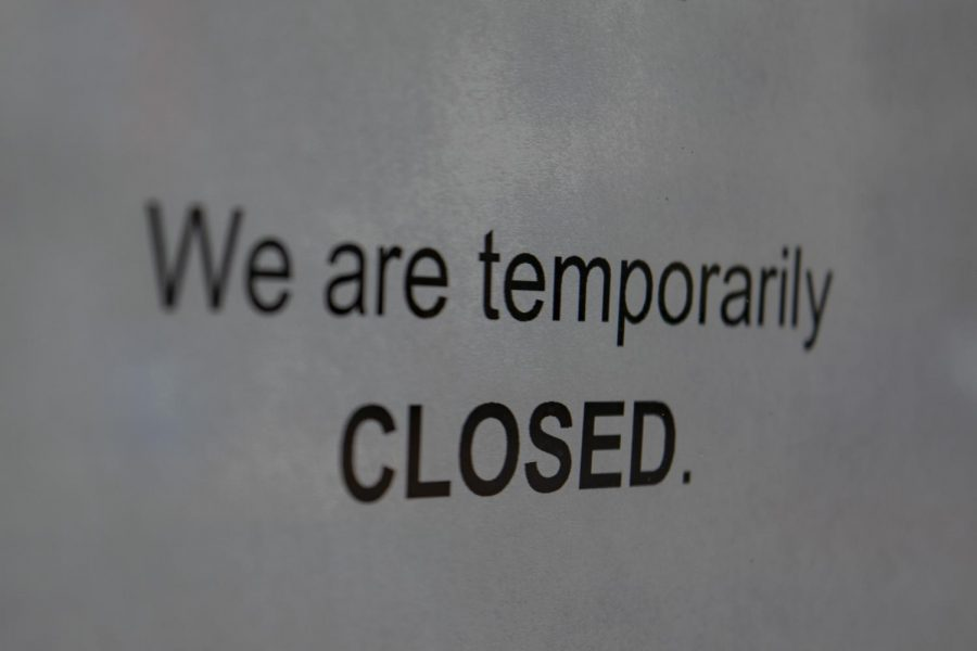 """Closed"" sign displayed in the window of a small business."